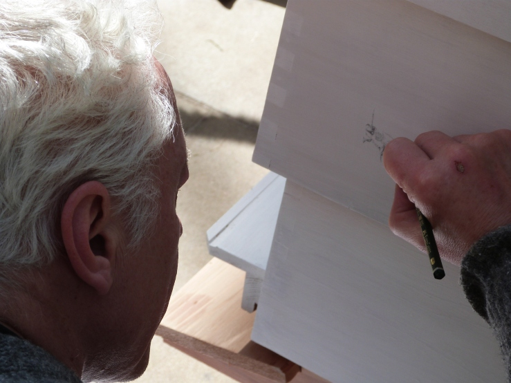 Paul Evans makes a drawing of a plasterer's bee directly onto the hive.